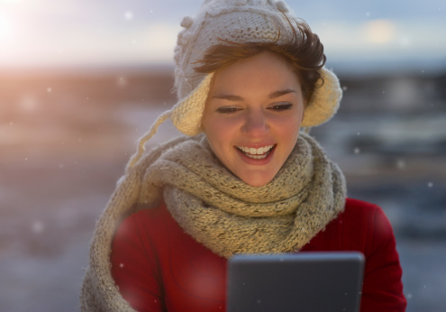 Woman using digital tablet in snow.