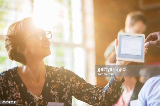 Woman using digital tablet in sunny meeting
