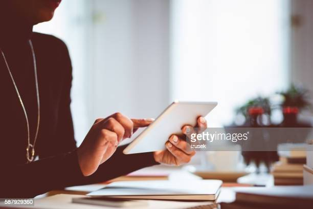 Woman using digital tablet indoors, close up of hands
