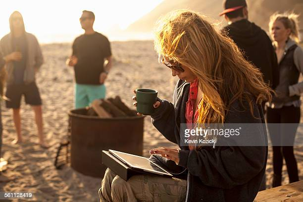 Woman using digital tablet on beach, friends in background