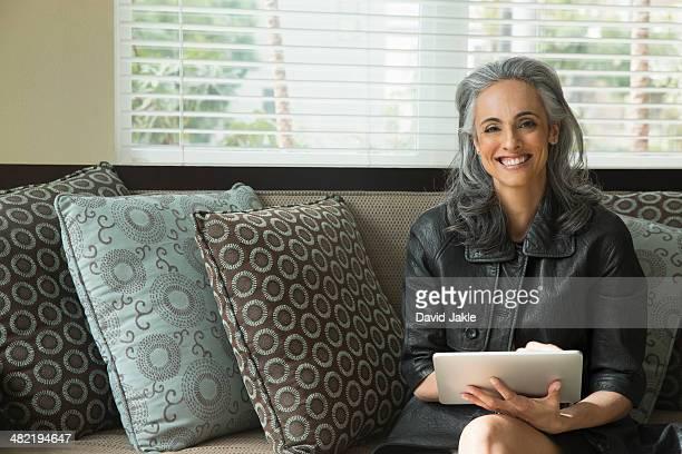 Woman using digital tablet on sofa