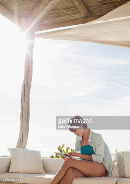 Woman using digital tablet on sunny patio