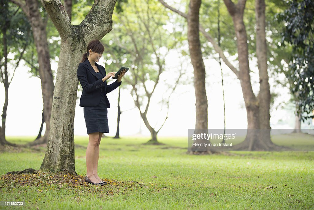 Woman using digital tablet outdoors in park : Stock Photo