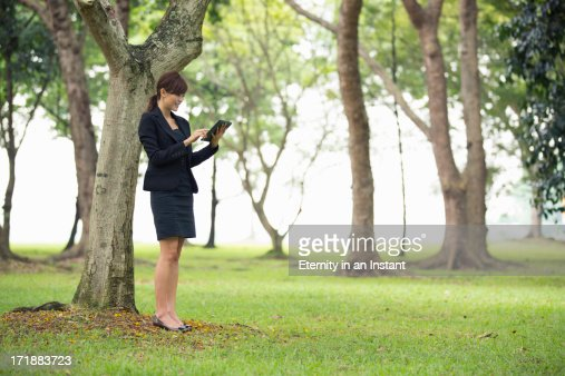 Woman using digital tablet outdoors in park : ストックフォト