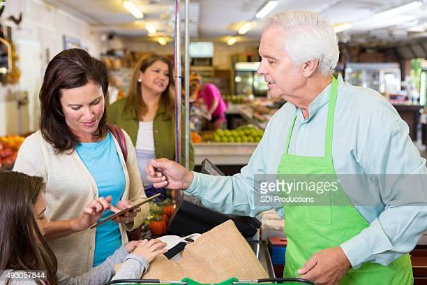 """Frau mit digitalen tablet, die Zahlung für Lebensmittel im """"The market"""""""