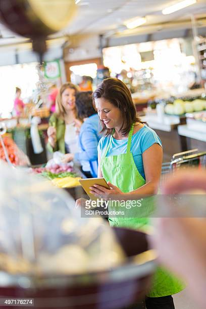 Woman using digital tablet while working in grocery store