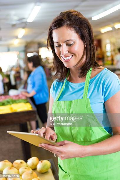 Woman using digital tablet while working in local grocery store