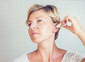 woman using ear drops on gray background