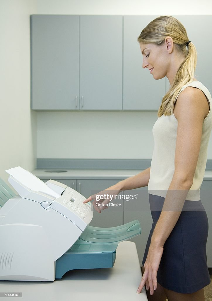 Woman using fax machine in office