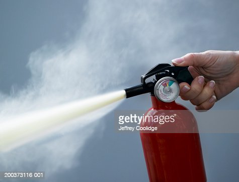 Woman using fire extinguisher, close-up