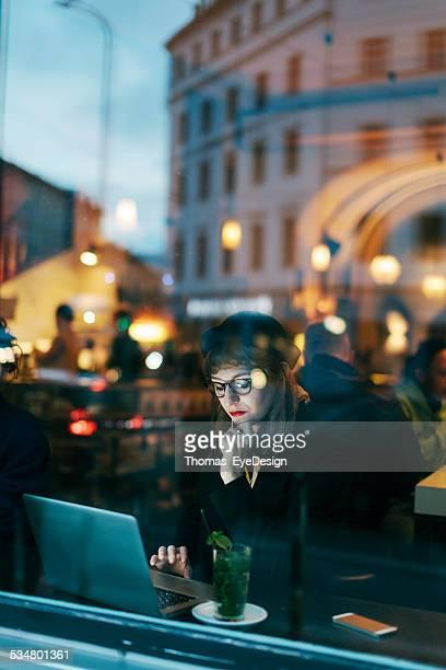 Frau mit kostenlosem W-LAN im Café