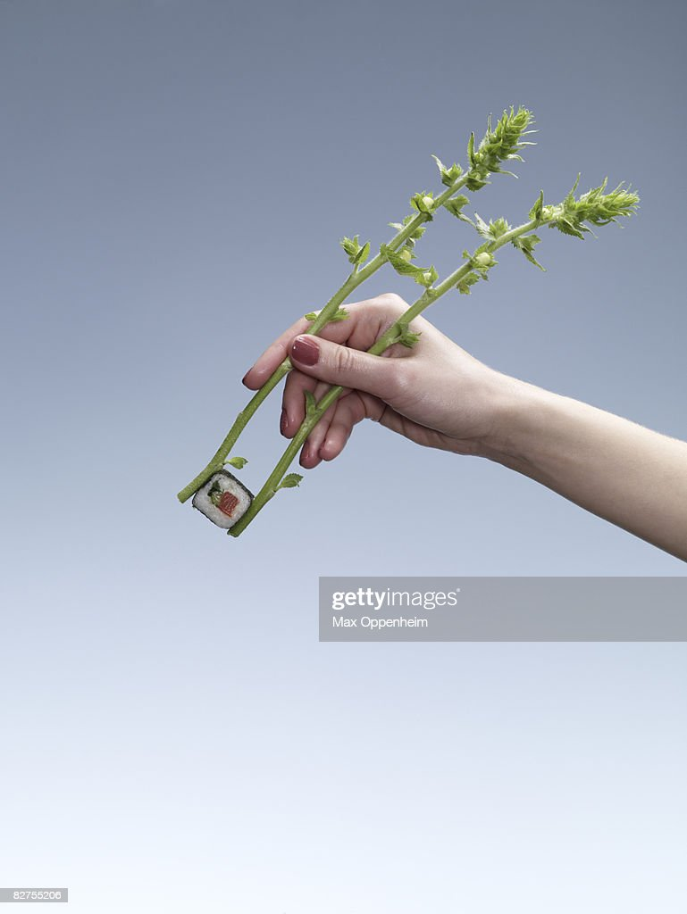 woman using fresh twigs as chopsticks : Stock Photo