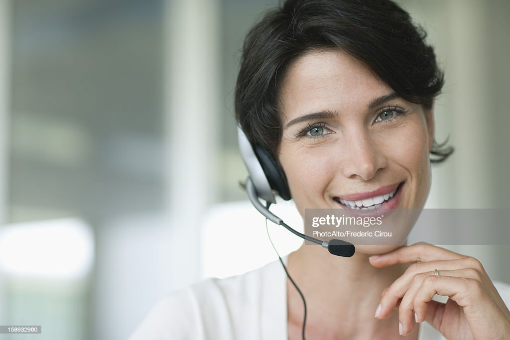 Woman using headset, smiling cheerfully : Stock Photo