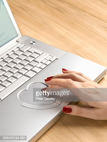 Woman using heart shaped  touch pad on laptop computer, close-up : Stock Photo
