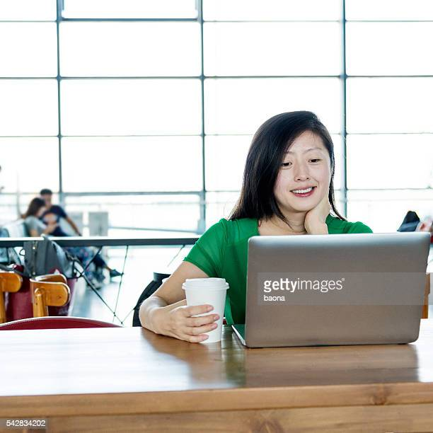 Woman using her laptop in airport lounge