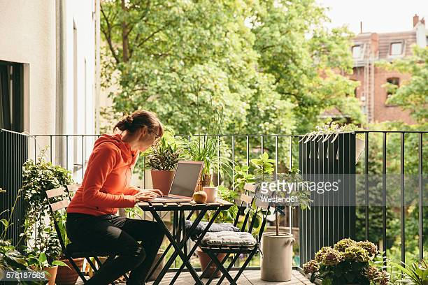 Woman using her laptop on balcony