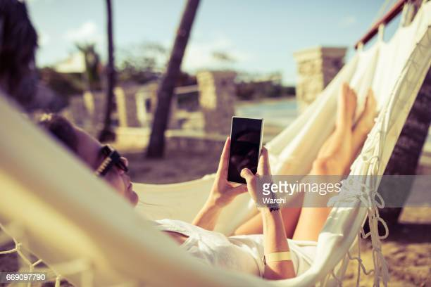Woman using her phone while relaxing in a hammock