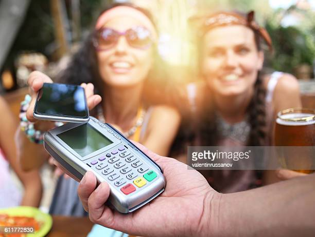 Woman using her smart phone for mobile payment in restaurant