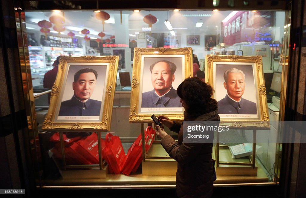 A woman using her smartphone walks past portraits of former Chinese leaders Zhou Enlai, from left, Mao Zedong and Liu Shaoqi displayed at a shop at night in Beijing, China, on Wednesday, March 6, 2013. China maintained its economic-growth target at 7.5 percent for 2013 while setting a lower inflation goal of 3.5 percent, setting up a challenge for new leaders to keep prices in check without harming expansion. Photographer: Tomohiro Ohsumi/Bloomberg via Getty Images