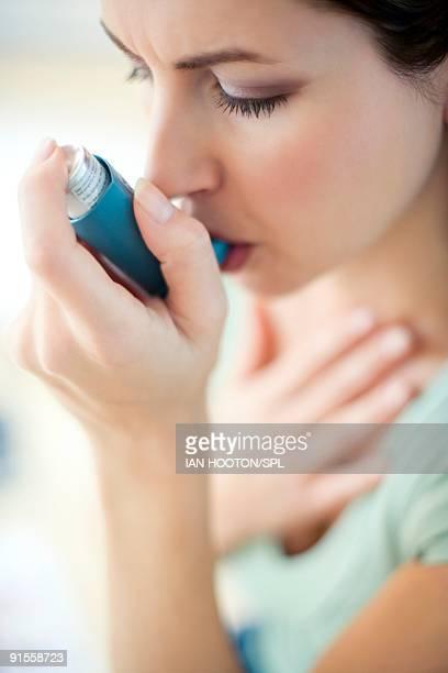 Woman using inhaler, close-up