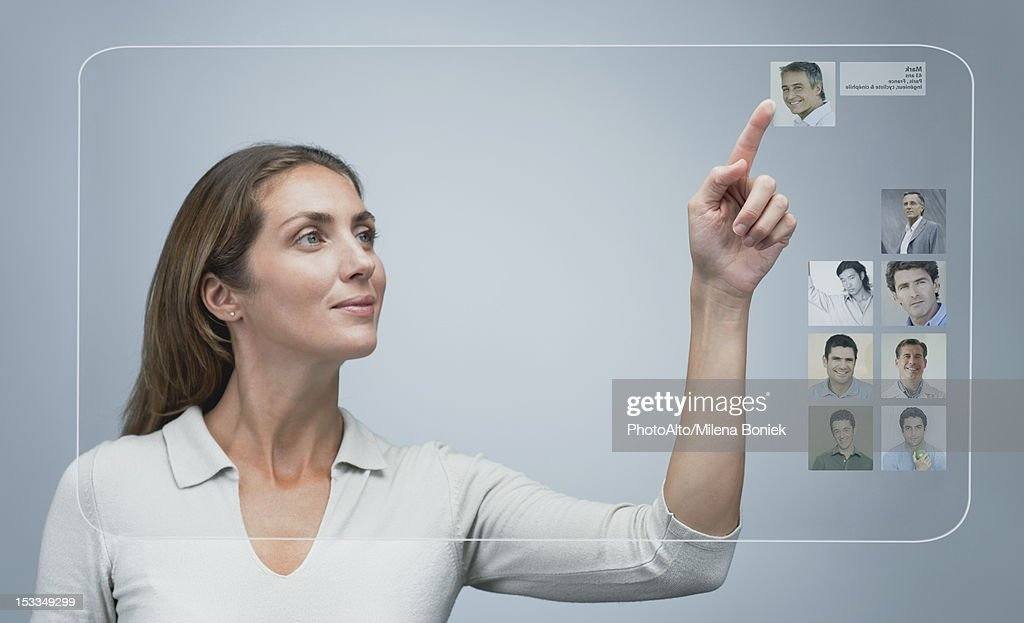 Woman using internet dating service on advanced touch screen interface : Stock Photo