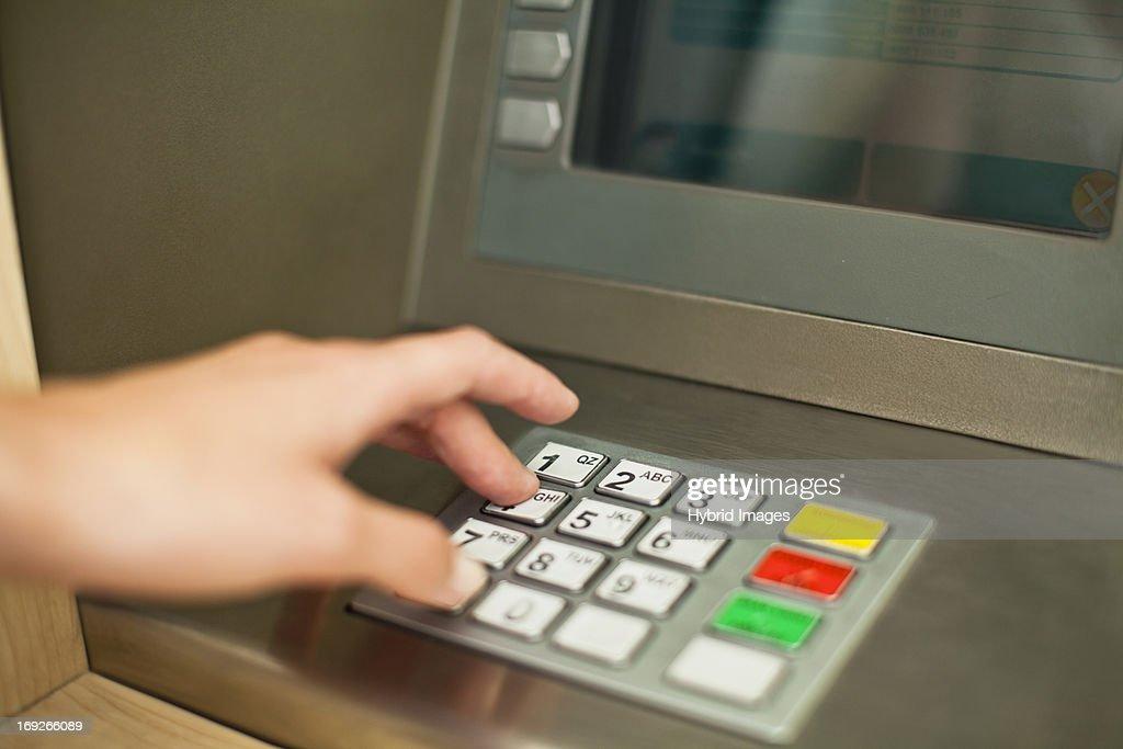 Woman using keypad on ATM