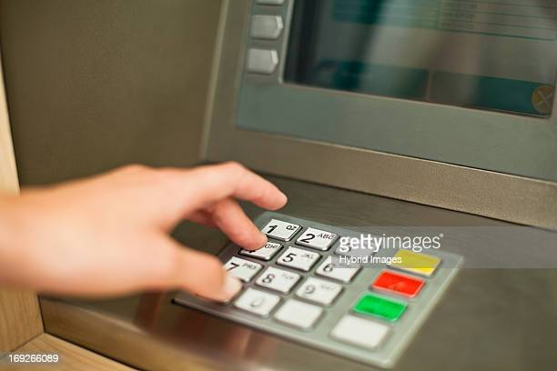 Woman using keypad on ATM