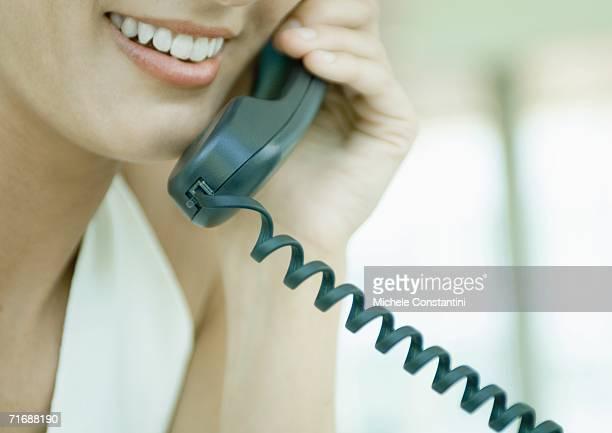 Woman using landline phone
