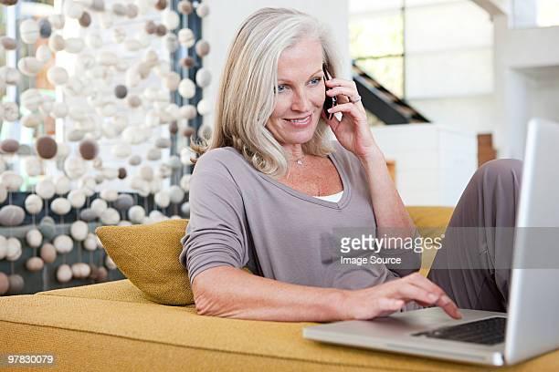 Femme à l'aide d'ordinateur portable et téléphone portable