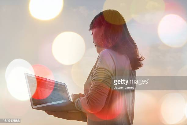 woman using laptop and lights