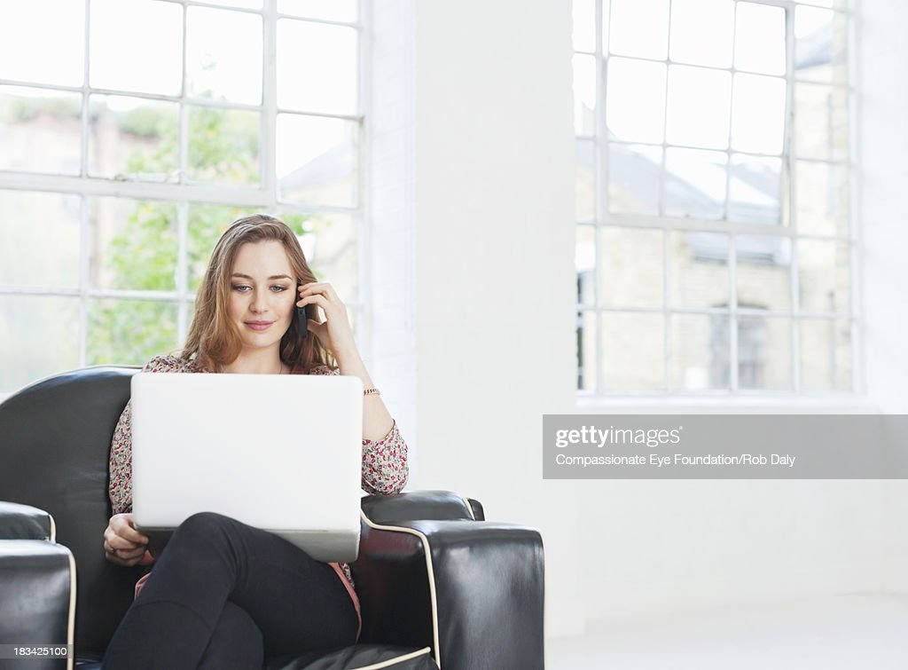 Woman using laptop and mobile phone in arm chair : Stock Photo