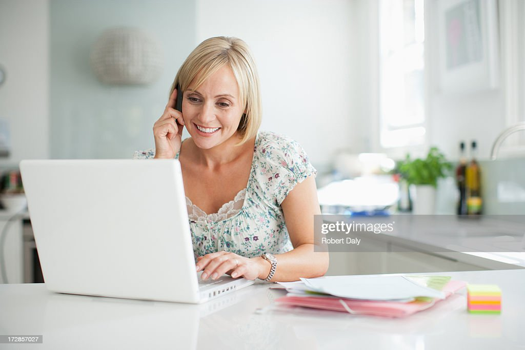 Woman using laptop and talking on cell phone : Stock Photo