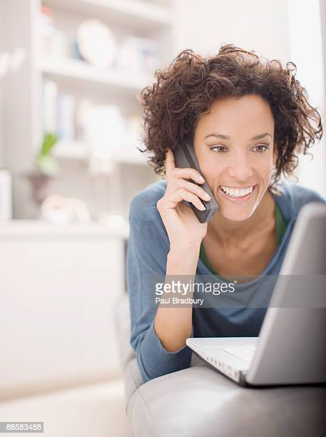 Woman using laptop and talking on telephone
