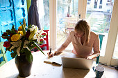 Woman Using Laptop At Dining Table Of Stylish Apartment