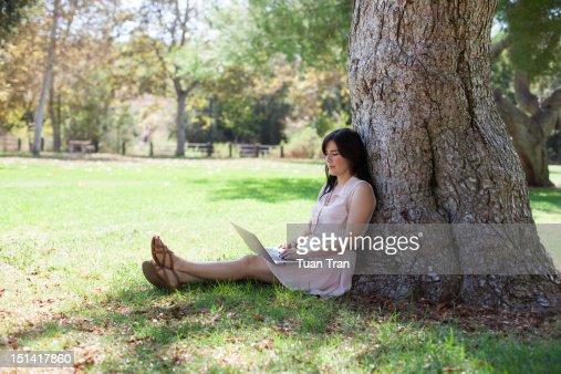 Woman using laptop at park : Photo