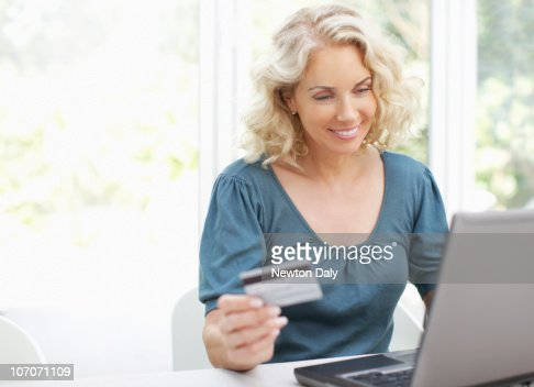 Woman using laptop, holding credit card, smiling : Stockfoto