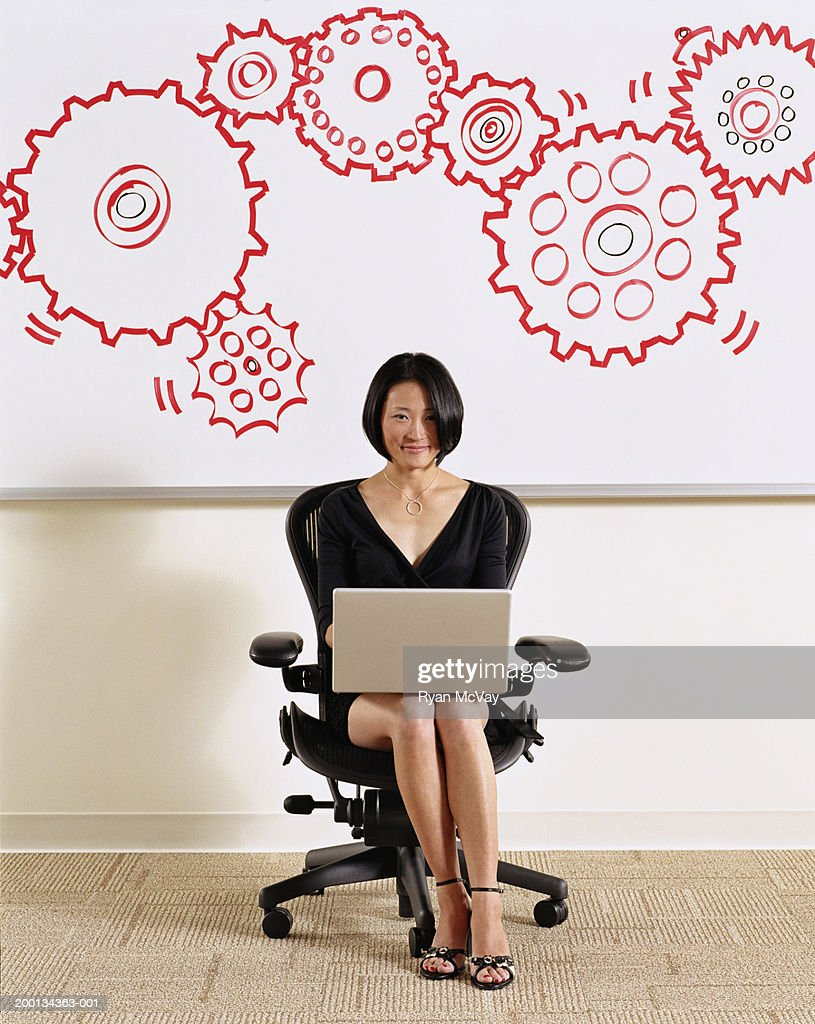 Woman using laptop, illustrated cogs on whiteboard in background : Stock Photo