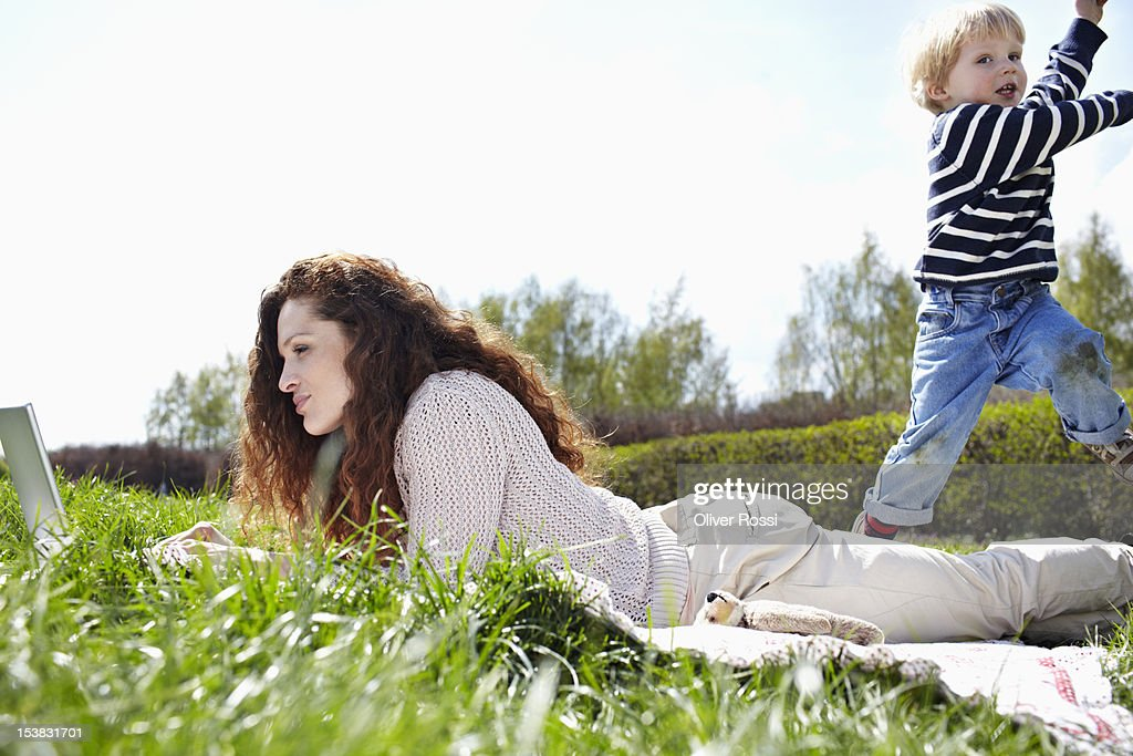 Woman using laptop in a meadow while her son plays : Stock Photo