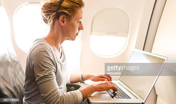 Frau mit Laptop im Flugzeug, während Flug