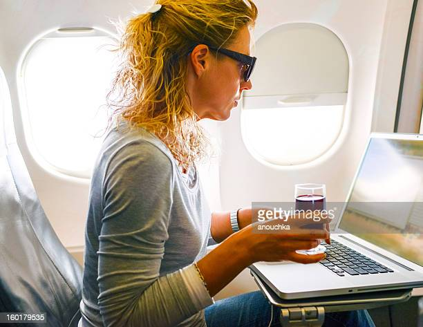 Femme à l'aide d'un ordinateur portable dans un avion pendant le vol