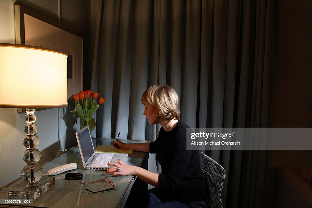Woman using laptop in apartment at night, side view : Stock Photo