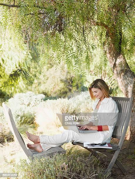 Frau mit laptop im Garten
