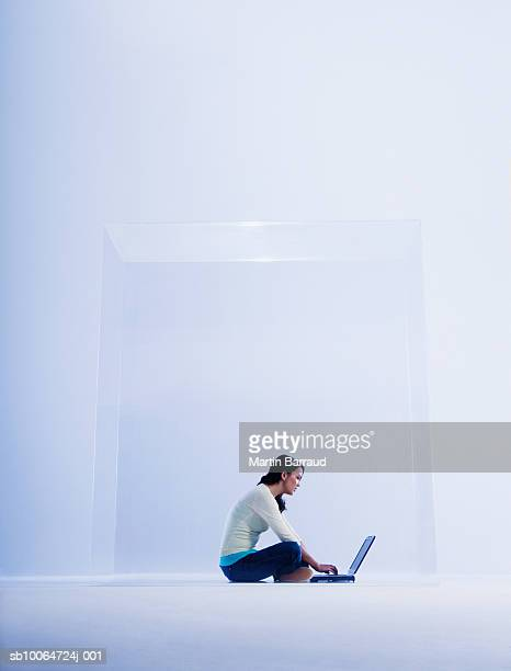 Woman using laptop in glass cabinet, side view