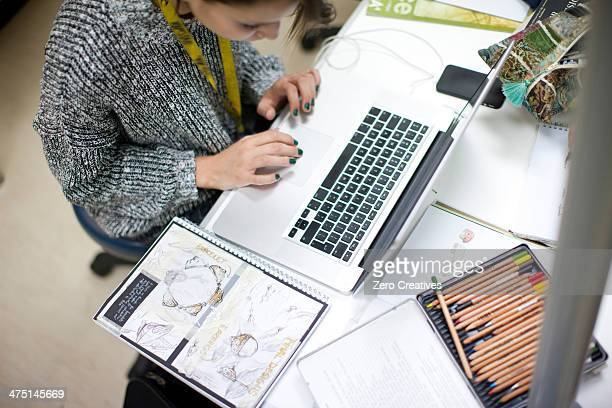 Woman using laptop in jewelery design class