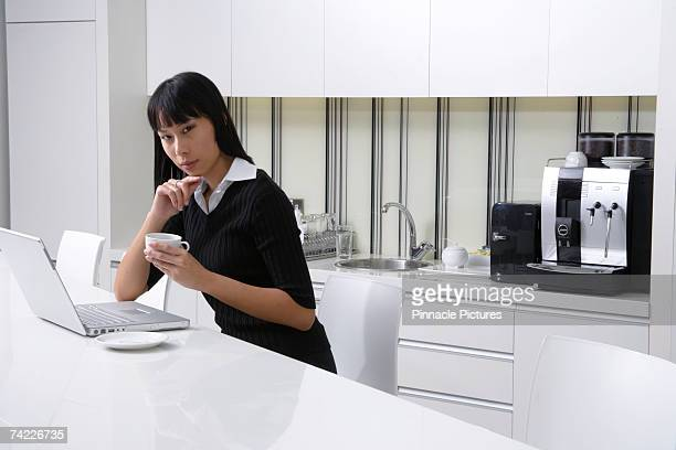 Woman using laptop in work kitchen drinking coffee