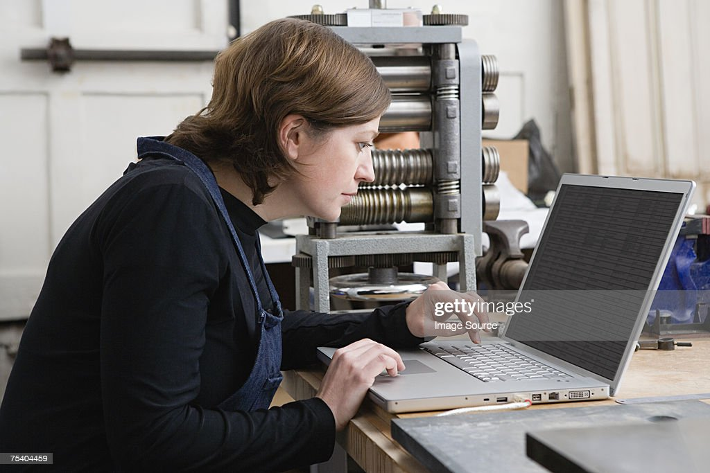 Woman using laptop in workshop : Stock Photo