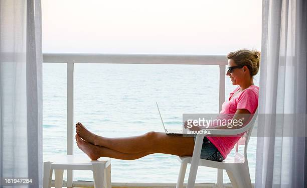 Woman using laptop on a balcony with ocean view