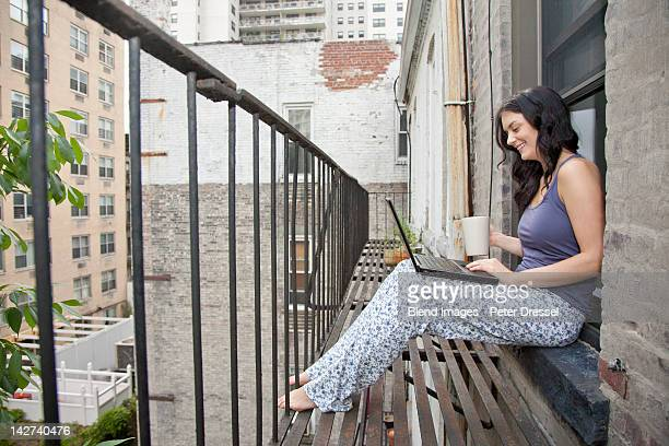 Woman using laptop on fire escape
