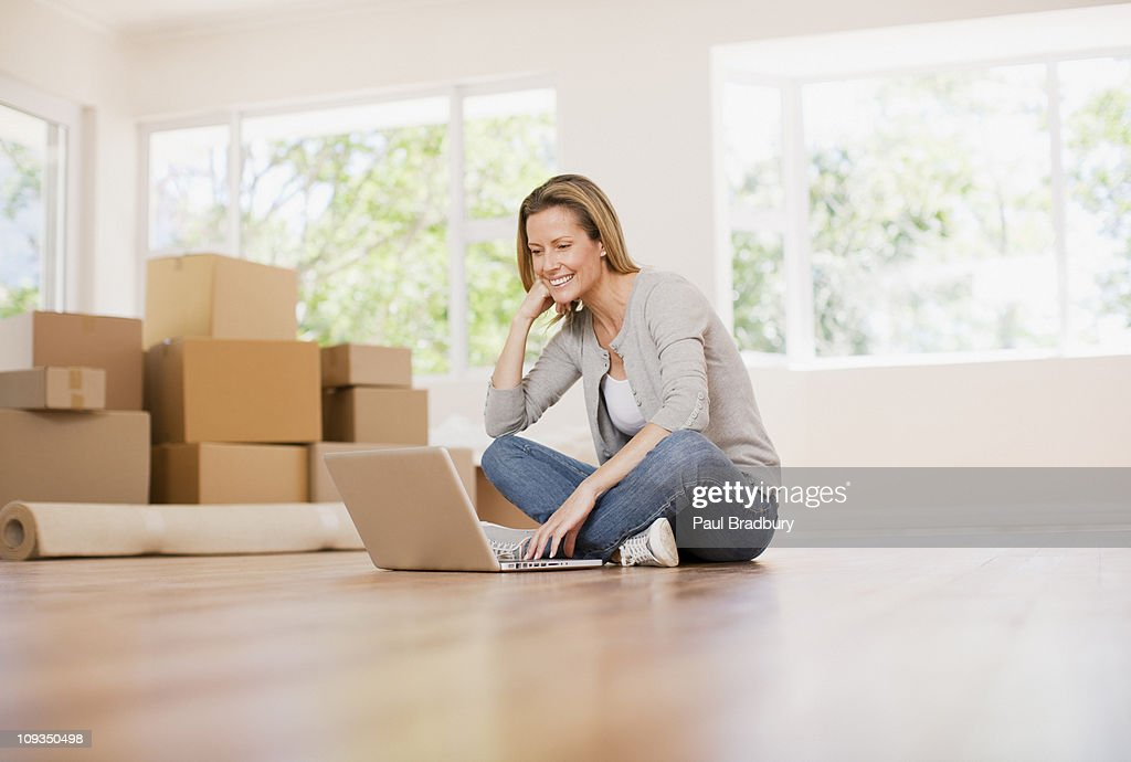 Woman using laptop on floor of her new house : Stock Photo