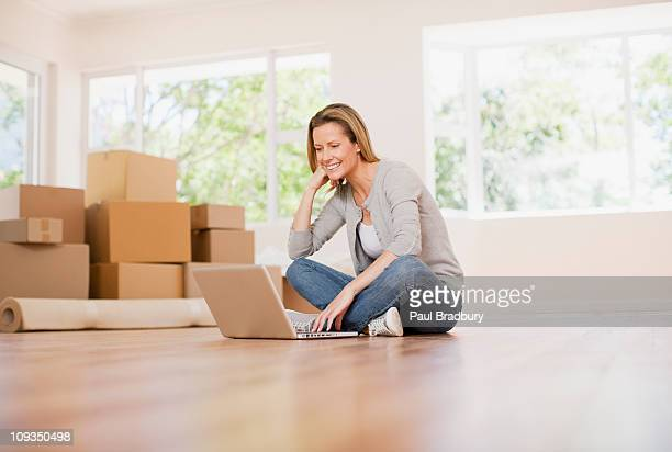Woman using laptop on floor of her new house